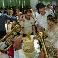 Trubači Balkanika sviraju ispred torte na svadbi